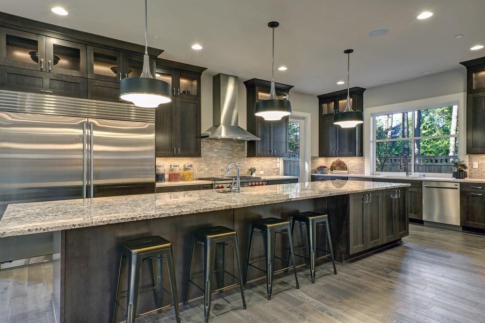 Modern Kitchen With Brown Kitchen Cabinets Oversized Kitchen Island With Bar Stools Granite Countertops Huge Refrigerator And Beige Backsplash